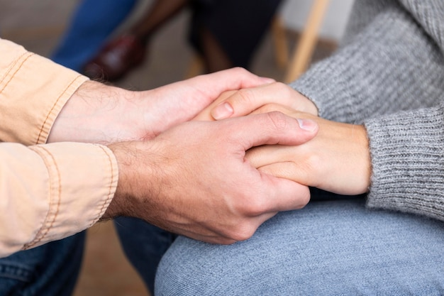 集団療法セッションで手をつないでいる人々