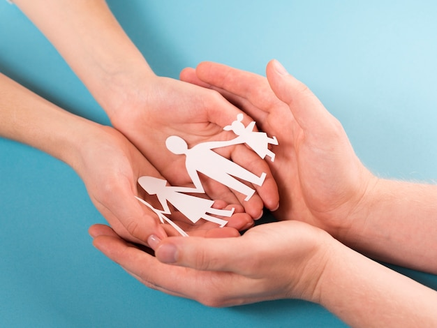 People holding in hands cute paper family