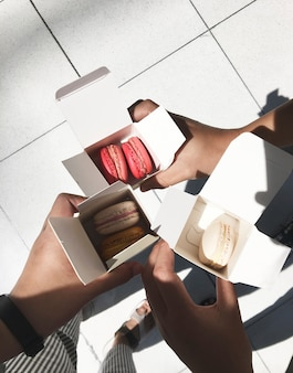 People holding macarons in box