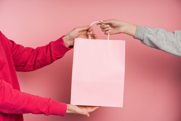 분홍색 종이 봉지를 들고 사람들.
