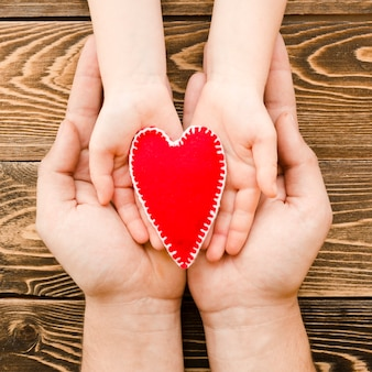 People holding a red heart in hands on wooden background