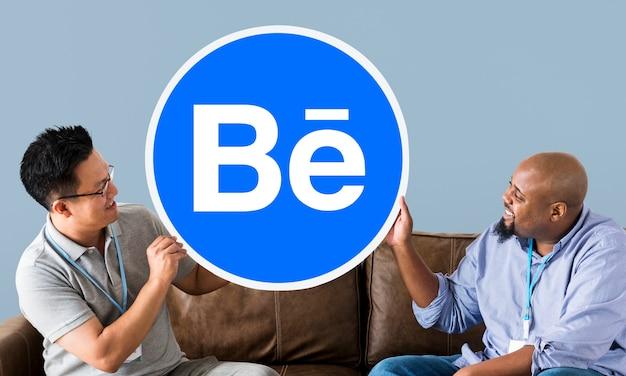 Люди, держащие логотип behance