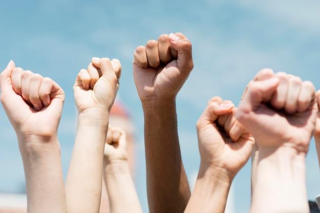 Люди держат кулаки в воздухе