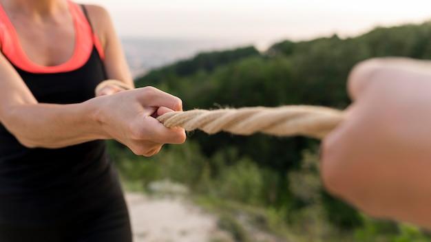 Люди держатся за веревку