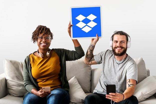 People holding up a dropbox icon