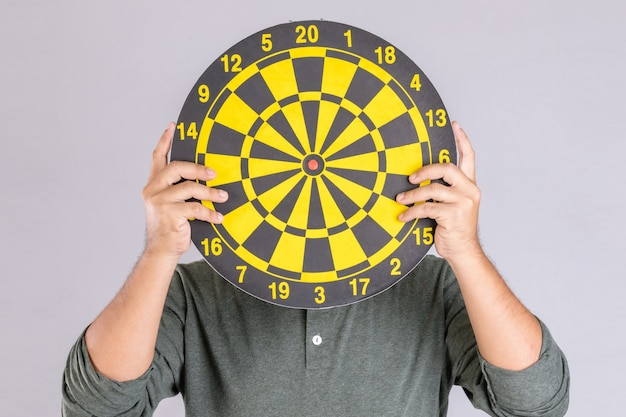 People holding yellow dartboard and hide his face.