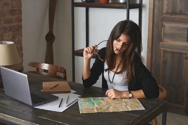 人、休日、観光のコンセプト。彼女の職場に座って、眼鏡をかみ、彼女の机の上の世界地図を見て、休暇を計画している魅力的な若いブルネットの女性サラリーマンの写真