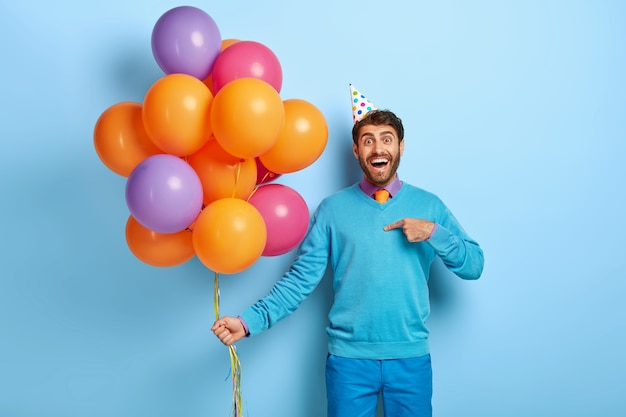 Persone e concetto di vacanza. l'uomo allegro dall'aspetto amichevole festeggia l'anniversario con amici e parenti