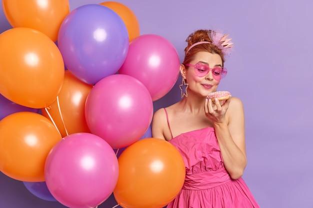 人々の休日とお祝いの概念。愛らしい赤い髪の若い女性は、紫色の背景の上に分離されたカラフルな風船の束を保持している食欲をそそるドーナツを見て