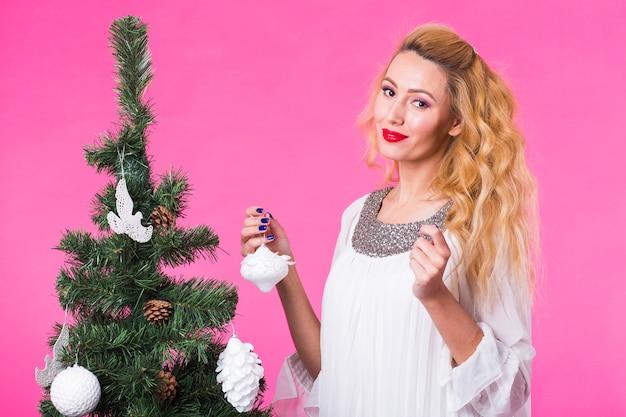 人、休日、クリスマスのコンセプト-ピンクの背景にクリスマスツリーを飾る女性