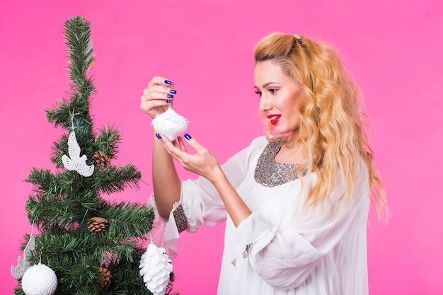 人、休日、クリスマスのコンセプト-ピンクの背景にクリスマスツリーを飾る若いブロンドの女性