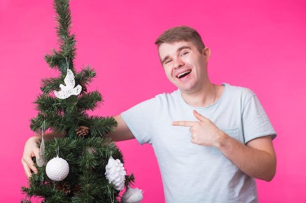 Люди, праздники и рождественские концепции - молодой человек украшает елку на розовом фоне