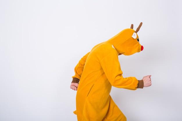 人、休日、クリスマスのコンセプト-白い壁で踊るサンタクロースの鹿の衣装の若い男