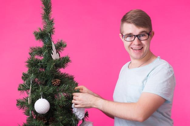 人、休日、クリスマスのコンセプト-ピンクの背景にクリスマスツリーの近くの若い笑顔の男