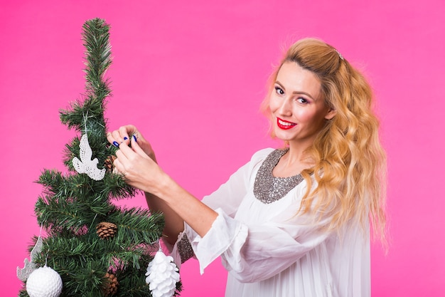 人、休日、クリスマスのコンセプト-ピンクの背景のクリスマスツリーにクリスマスボールを置く若い女性。