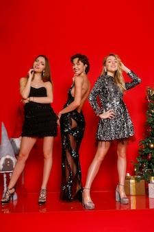사람, 휴일, 글래머 컨셉 - 밤새도록 춤추자! 새해를 축하하는 세 명의 쾌활한 젊은 똑똑한 여성, 빨간색 배경 위에 크리스마스, 포즈