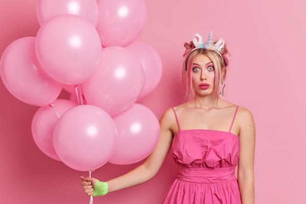 人々の休日のお祝いのコンセプト。ショックを受けた美しい女性がお祝いのドレスを着ているユニコーンのカチューシャは誕生日を祝い、パーティーは膨らませた風船の束を持っている