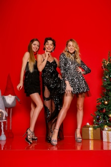 People, holidays, and glamour concept - let's dance all night! full length of three cheerful young smartly dressed women celebrating new year, christmas over red background, posing