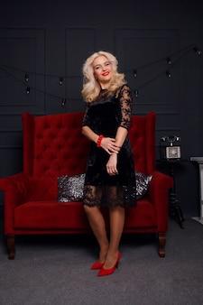 Люди, праздники, ювелирные изделия и роскошное понятие - красивая брюнетка, элегантный женский портрет. ретро леди с красными губами макияж, волнистая прическа, ювелирные изделия из драгоценных камней моды, позирующие в современной кровати в интерьере