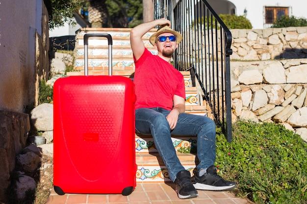 人、休日、旅行、休息のコンセプト。彼のスーツケースの近くの階段に座っている若い男