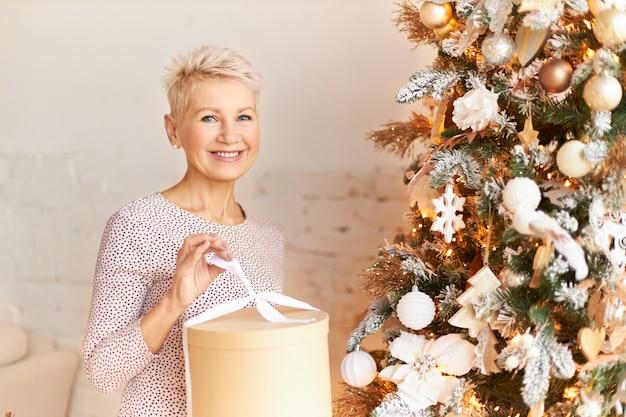 Persone, vacanze, vacanze e concetto di umore festivo. ritratto della femmina matura felice attraente nella scatola piacevole della tenuta del vestito, regalo di disimballaggio del nuovo anno da suo marito che indovina che cosa dentro