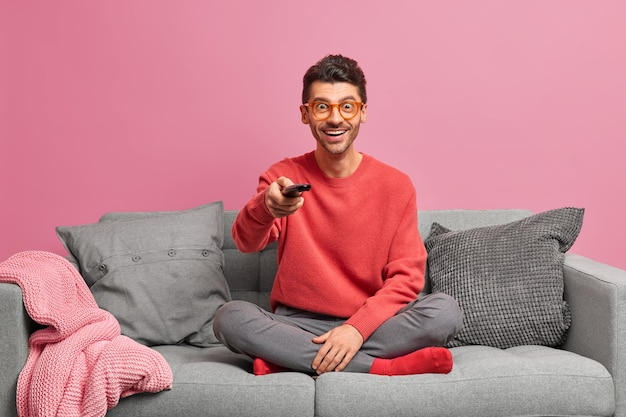 사람들이 가정 생활 레저 개념. 쾌활한 편안한 남자가 편안한 소파에 로터스 포즈에 앉아 원격 제어를 보유하고 있습니다.