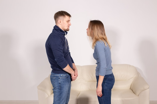 People, home violence and abuse concept - young couple screaming to each other on white background.