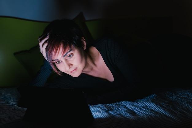 사람들은 잠자리에 들기 전에 엔터테인먼트 장치를 연결했습니다. 밤에 침대에서 온라인 tv 쇼를보고 젊은 여자. 기술 및 레저 개념. 젊은이들을위한 집에서의 라이프 스타일.