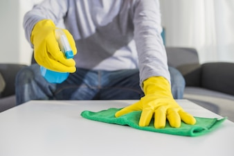People, housework and housekeeping concept - close up of man hands cleaning table with cloth and detergent spray at home
