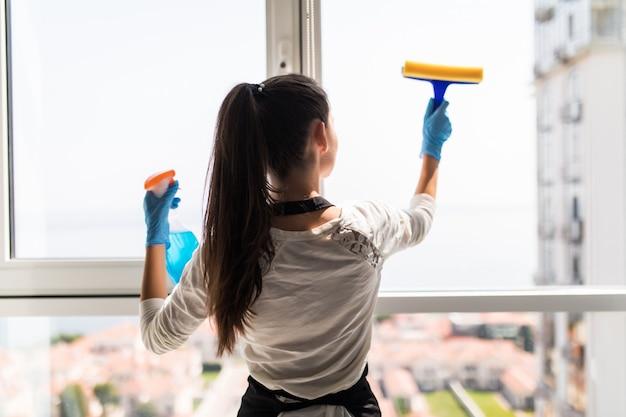Люди, работа по дому и уборка концепции. счастливая женщина в перчатках очищая окно с брызгом тряпки и моющего средства дома