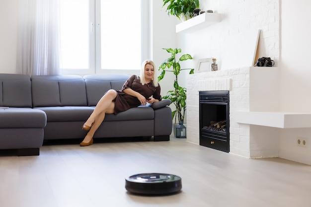 사람, 집안일 및 기술 개념-행복한 여자와 로봇 진공 청소기