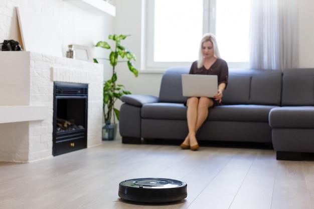 사람, 집안일 및 기술 개념 pc 컴퓨터와 로봇 진공 청소기로 행복한 여자
