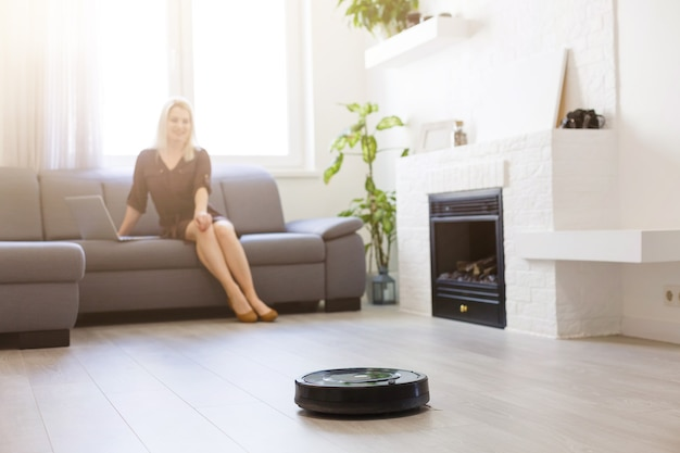 人、家事、技術の概念-pcコンピューターとロボット掃除機を持つ幸せな女性