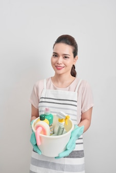 People, housework and housekeeping concept - happy woman holding cleaning stuff at home
