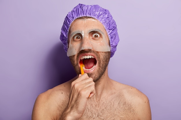 People, hygiene and morning routine concept. close up shot of young man brushes teeth with toothbrush, keeps mouth opened, wears bathcap, beauty mask on face