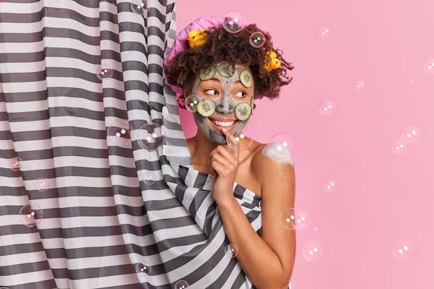 Persone igiene benessere concetto di cura della pelle. felice donna afroamericana guarda positivamente da parte applica maschera di argilla con fette di cetriolo fa la doccia in bagno si trova dietro la tenda si diverte a lavarsi