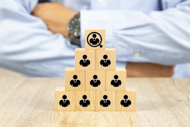 People icon on cube wooden toy blocks stacked in a pyramid shape