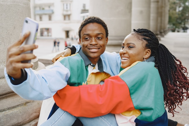 People in identifical clothes. african couple in autumn city. people sitting and uses phone.