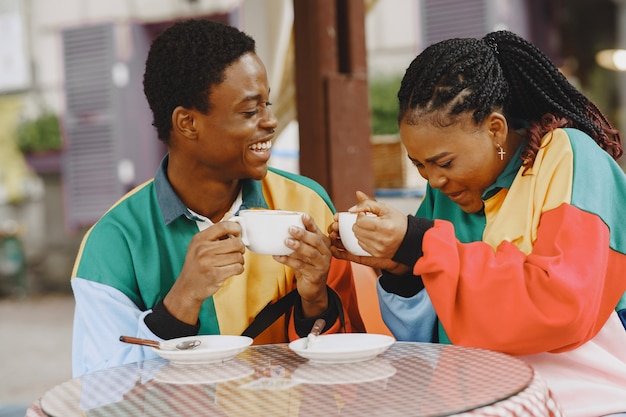 People in identifical clothes. african couple in autumn city. people at the table.