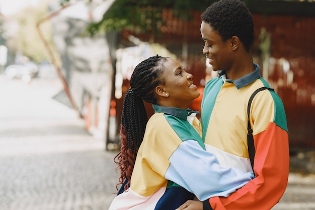 People in identifical clothes. african couple in autumn city.