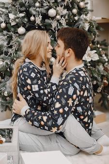 Люди в украшениях christman. мужчина и женщина в одинаковых пижамах. семья дома.