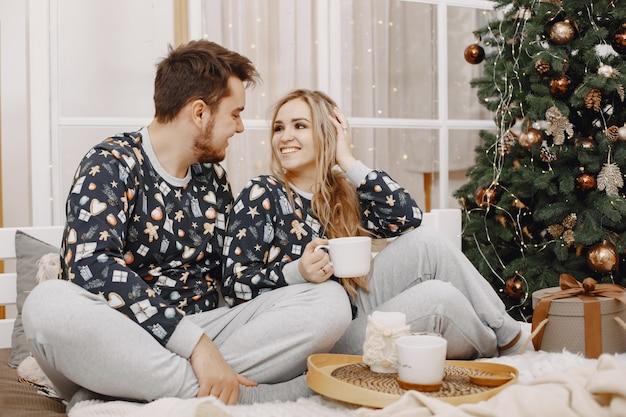 Christman 장식의 사람들. 남자와 여자의 고유 한 잠옷. 침대에 가족.