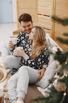 Люди в украшениях christman. мужчина и женщина в одинаковых пижамах. семья на кровати.