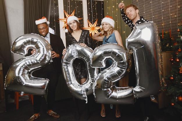 Christman 장식의 사람들. 검은 양복에 남자. 그룹 축하 새해. 풍선을 가진 사람들 2021.