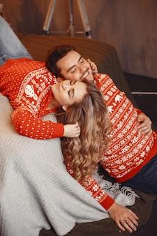 크리스마스 장식에있는 사람들. 빨간 스웨터에 남자와 여자.