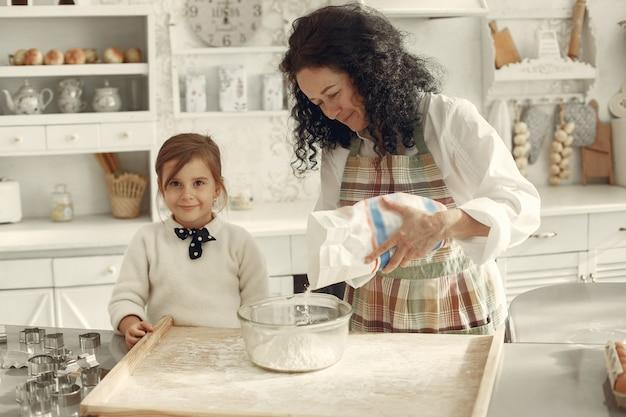 부엌에있는 사람들. 작은 딸과 함께 할머니입니다. 성인 여자는 요리하는 어린 소녀를 가르칩니다.