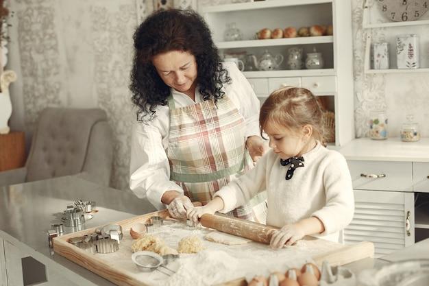 台所の人々。小さな娘を持つ祖母。大人の女性は小さな女の子に料理を教えます。