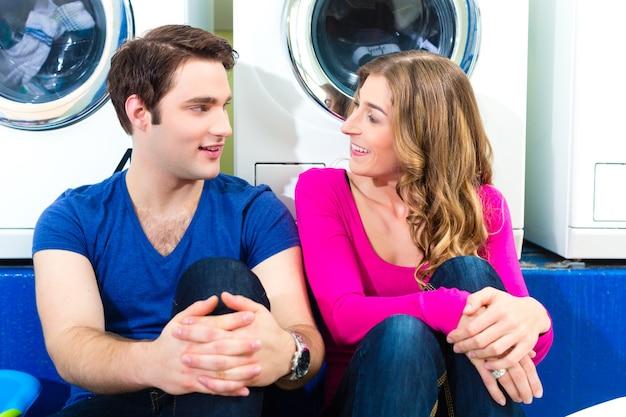 빨래방에있는 사람들, 더러운 세탁물 씻기, 세탁기 앞에 앉아 함께 이야기하기