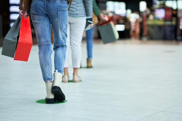 検疫中/流行中の社会的距離にあるスーパーマーケット/モールの列/列に並んでいる人々