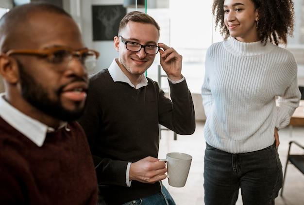 コーヒーを飲みながら話し合う会議の人々